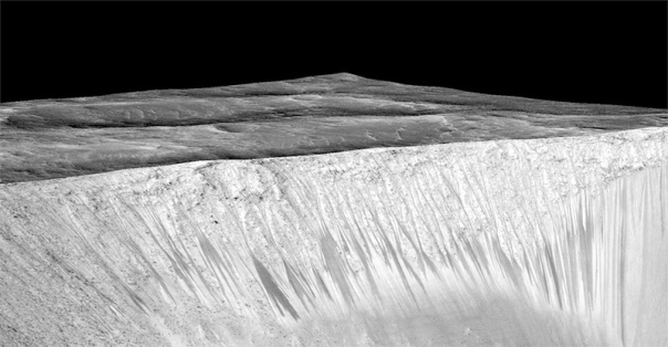 Dark narrow streaks called recurring slope lineae emanate out of the walls of Garni crater on Mars. The dark streaks here are up to few hundred meters in length. They are hypothesised to be formed by flow of briny liquid water on Mars.